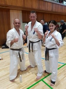 three taekwondo fighters in different belts and ages